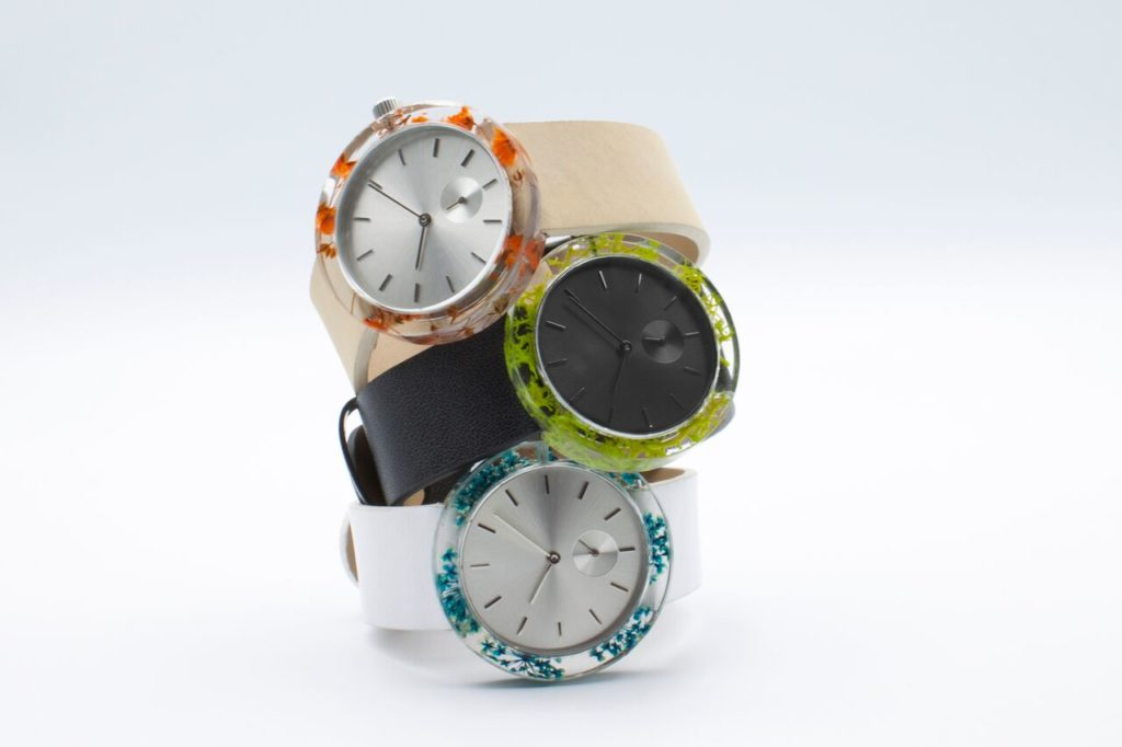 The Botanist Watch by Analog with natural moss, flowers in the resin case. $109.